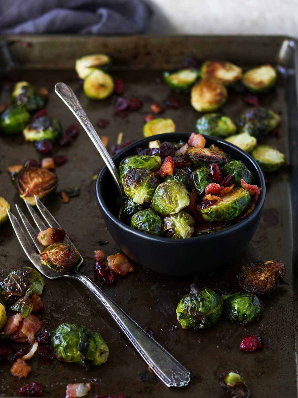 Brussels Sprouts with Bacon and Cranberries on a sheet pan and in a black bowl - Food Styling